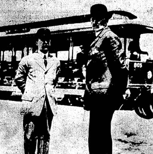 Two Titanic stewards standing in front of a tram
