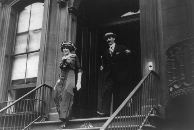 Madeleine Astor on the left and John Jacob Astor on the right descending the steps of a New York building.